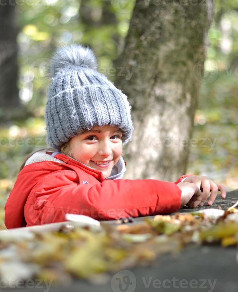 junges Mädchen im Park, das den Charme des Herbstes genießt foto
