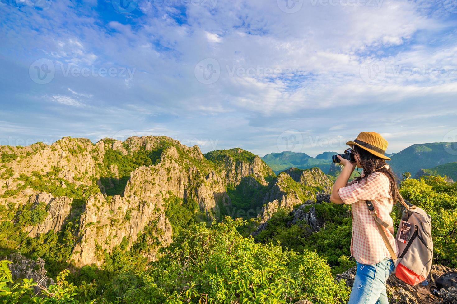 Wanderfrau mit Kamera genießen die Aussicht bei Sonnenaufgang foto