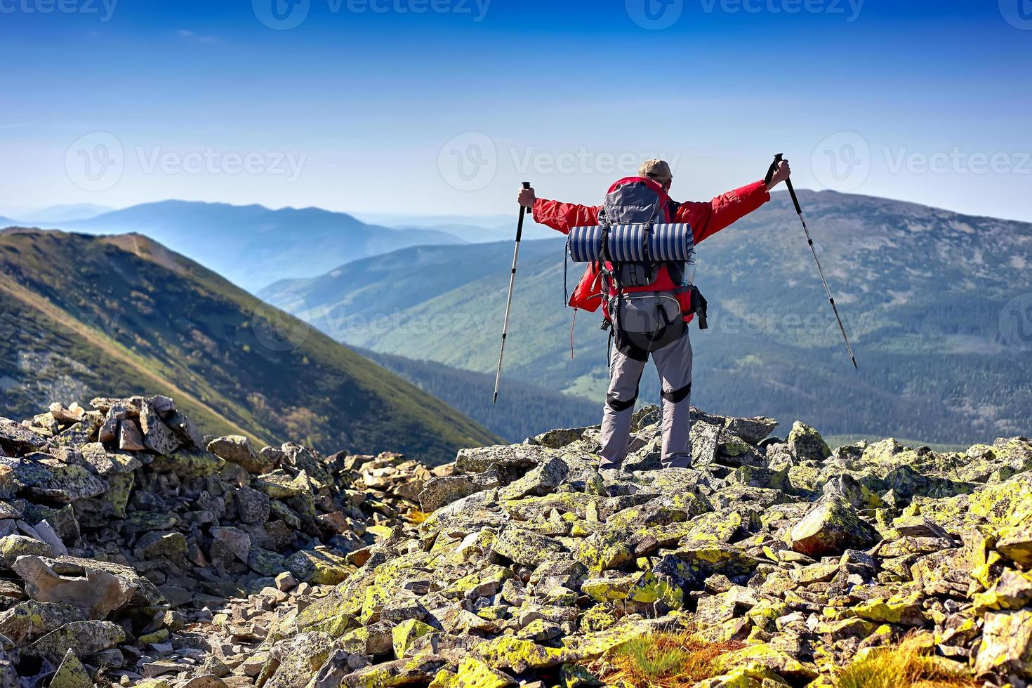 Wanderer mit Rucksack in den Bergen stehen und die v genießen foto