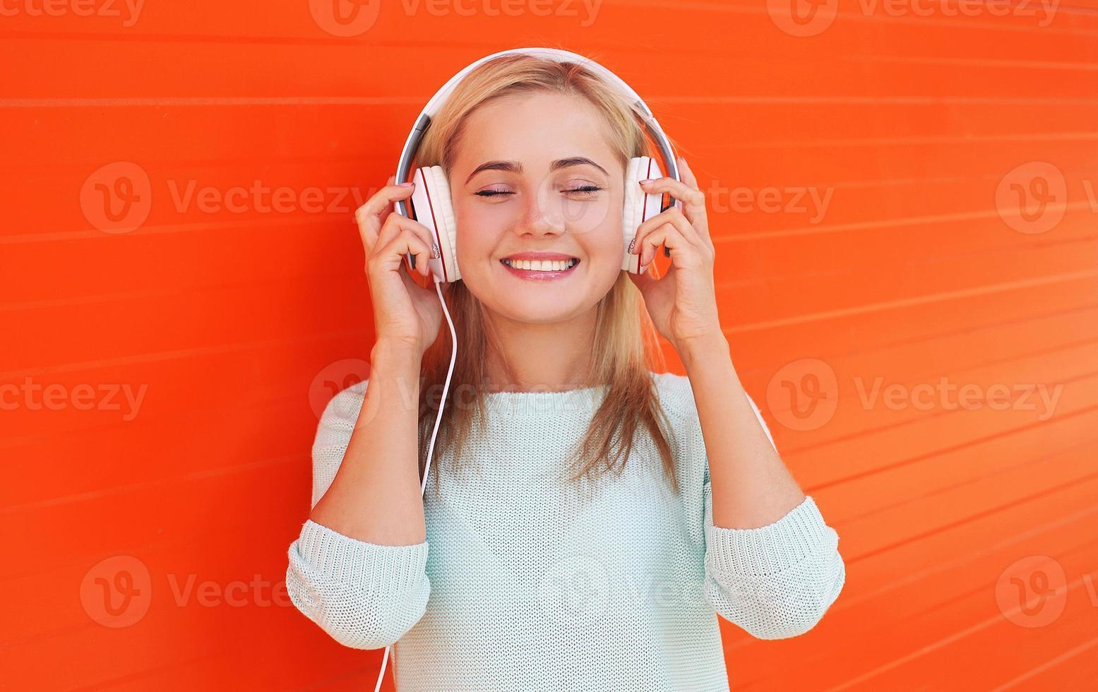 hübsche junge Frau hört zu und genießt die Musik in Kopfhörern foto