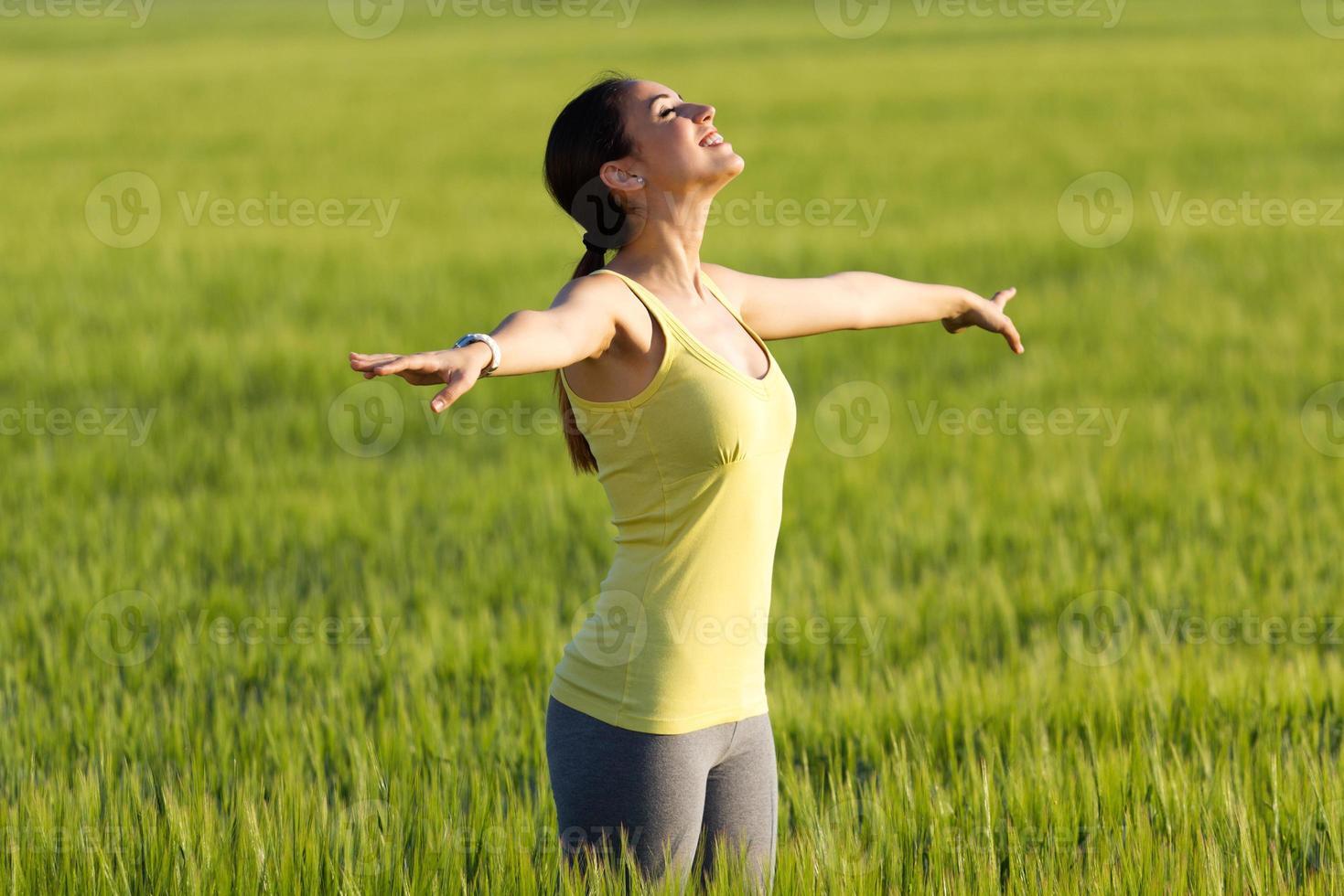junge Frau, die den Frühling genießt, der in einem Getreidefeld steht foto
