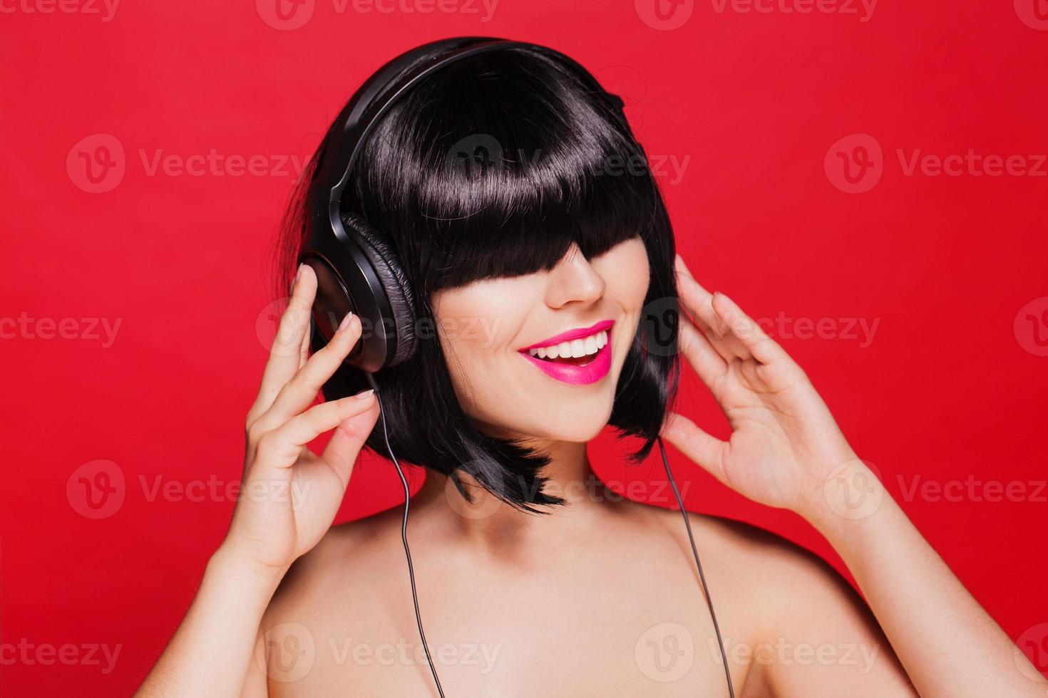 Frau hört Musik über Kopfhörer und genießt einen Gesang. Nahansicht foto