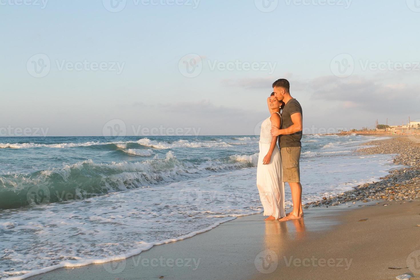 junges Paar geht gerne in der Abenddämmerung an einem dunstigen Strand spazieren foto