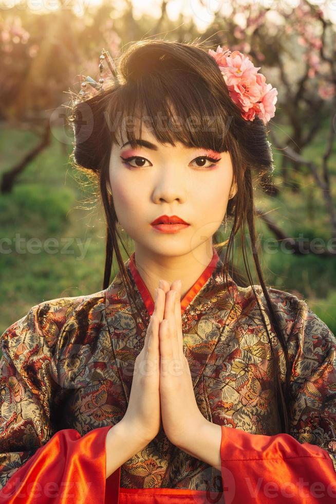 schöne asiatische Frau in Sakura-Blüte foto