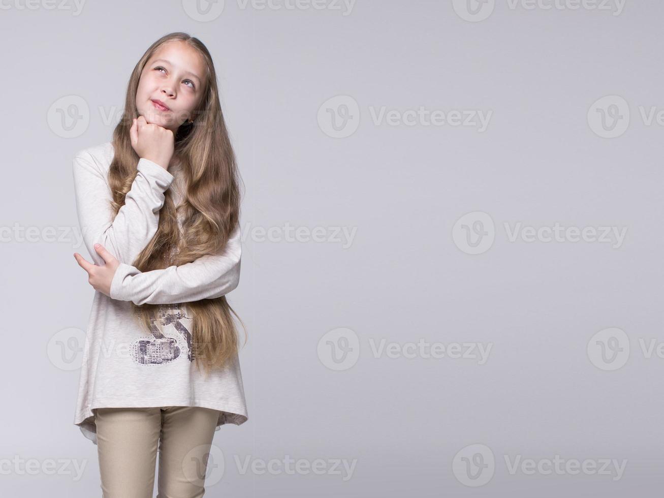 Porträt des verwirrten Teenager-Mädchens, das auf einem grauen Hintergrund steht foto
