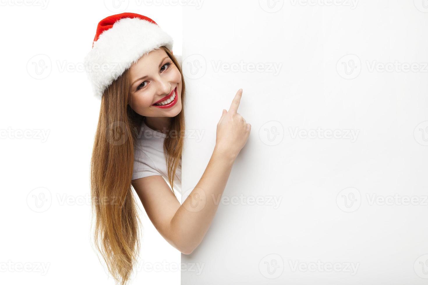 Weihnachtsfrau in der Weihnachtsmütze, die leeres Brett zeigt foto
