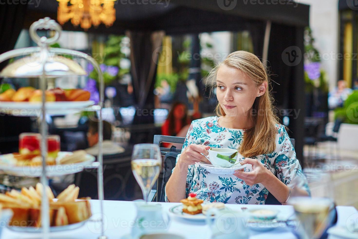 schöne junge Frau, die Nachmittagstee genießt foto