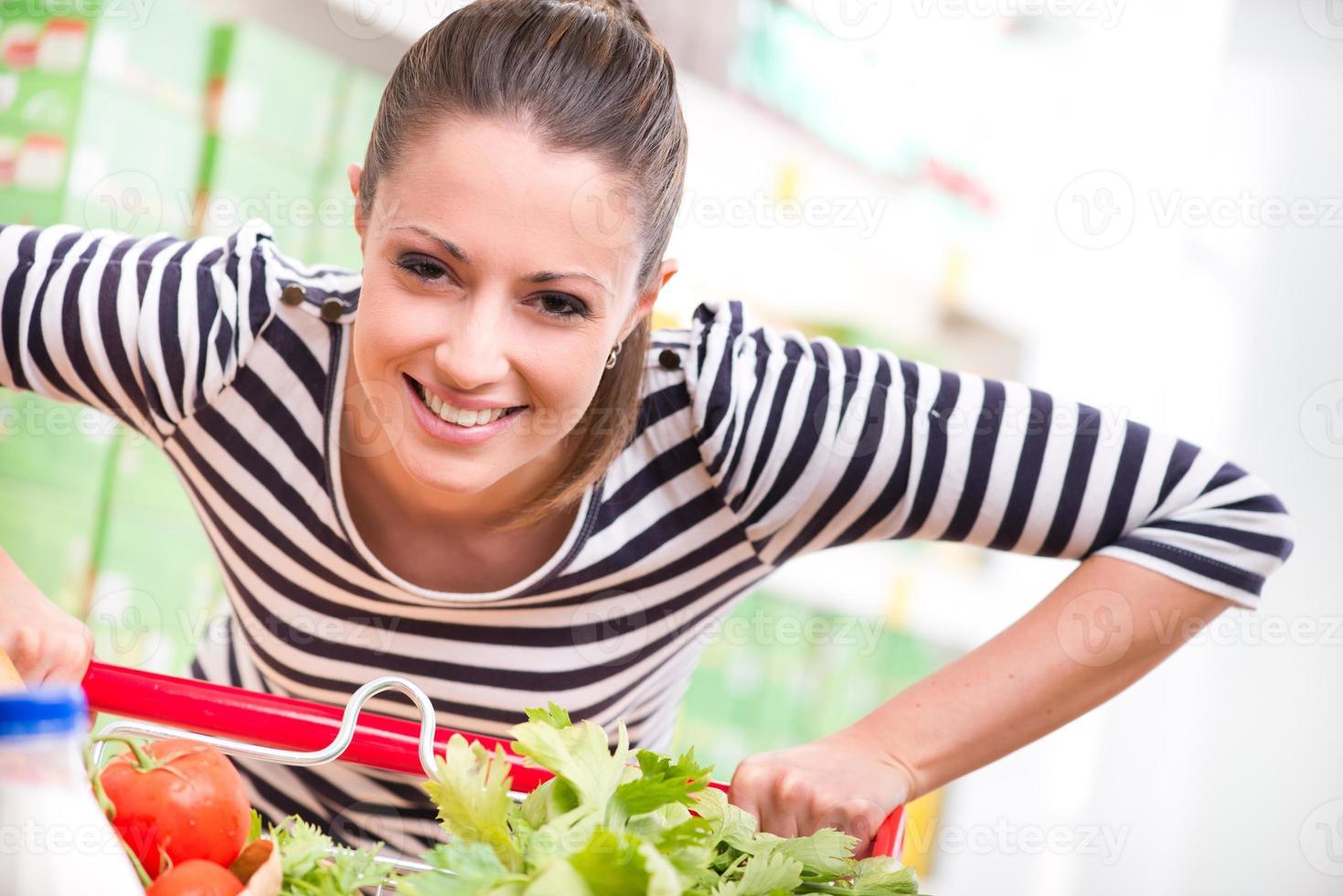 Frau genießt das Einkaufen im Supermarkt foto