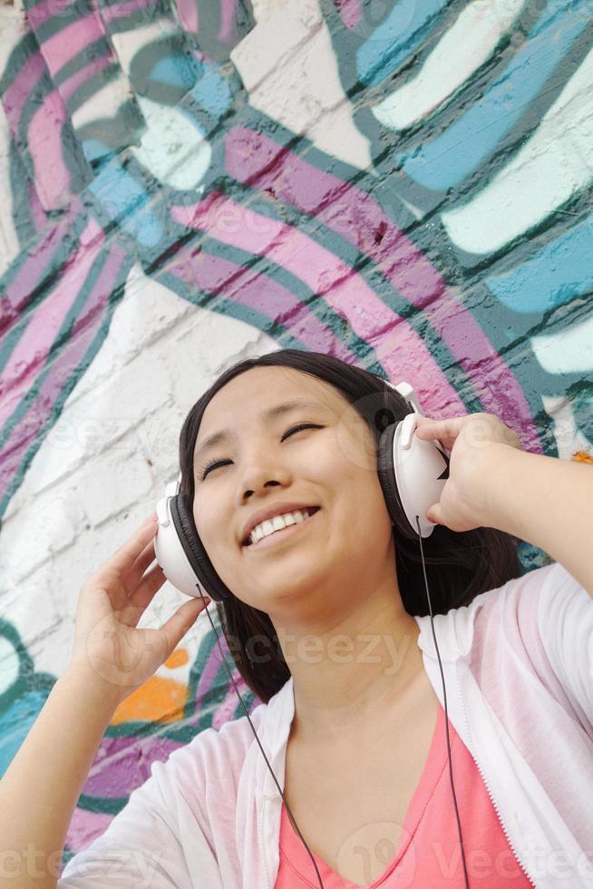 junge lächelnde Frau, die ihre Kopfhörer beim Genießen des Hörens hält foto