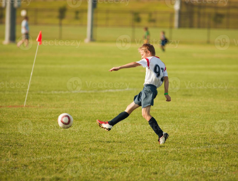 kleiner Fußballspieler, der den Ball ins Tor tritt foto
