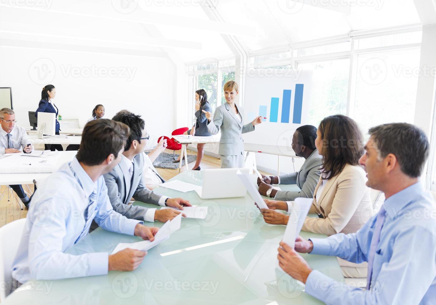 Geschäftspräsentation einer korporativen Frau gegenüber ihren Kollegen foto