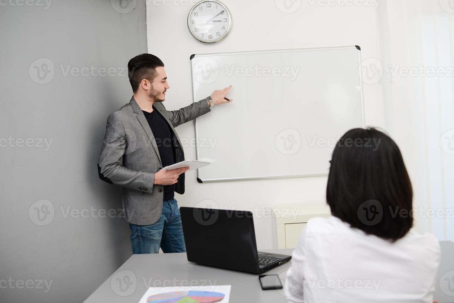 junger Geschäftsmann oder Lehrer, der Daten auf weißer Tafel zeigt foto