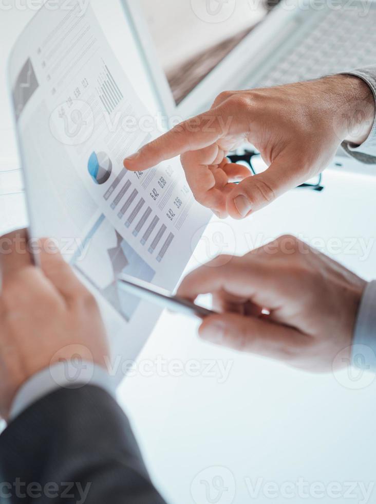 Geschäftsleute, die einen Finanzbericht prüfen foto
