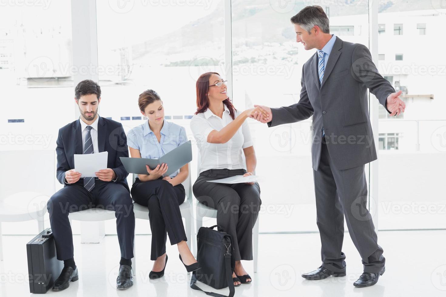 lächelnder Geschäftsmann, der Mitarbeiterhand schüttelt foto
