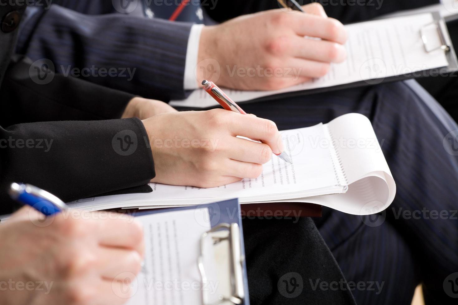 Männer, die sich auf einer Arbeitskonferenz mit Stift und Papier Notizen machen foto