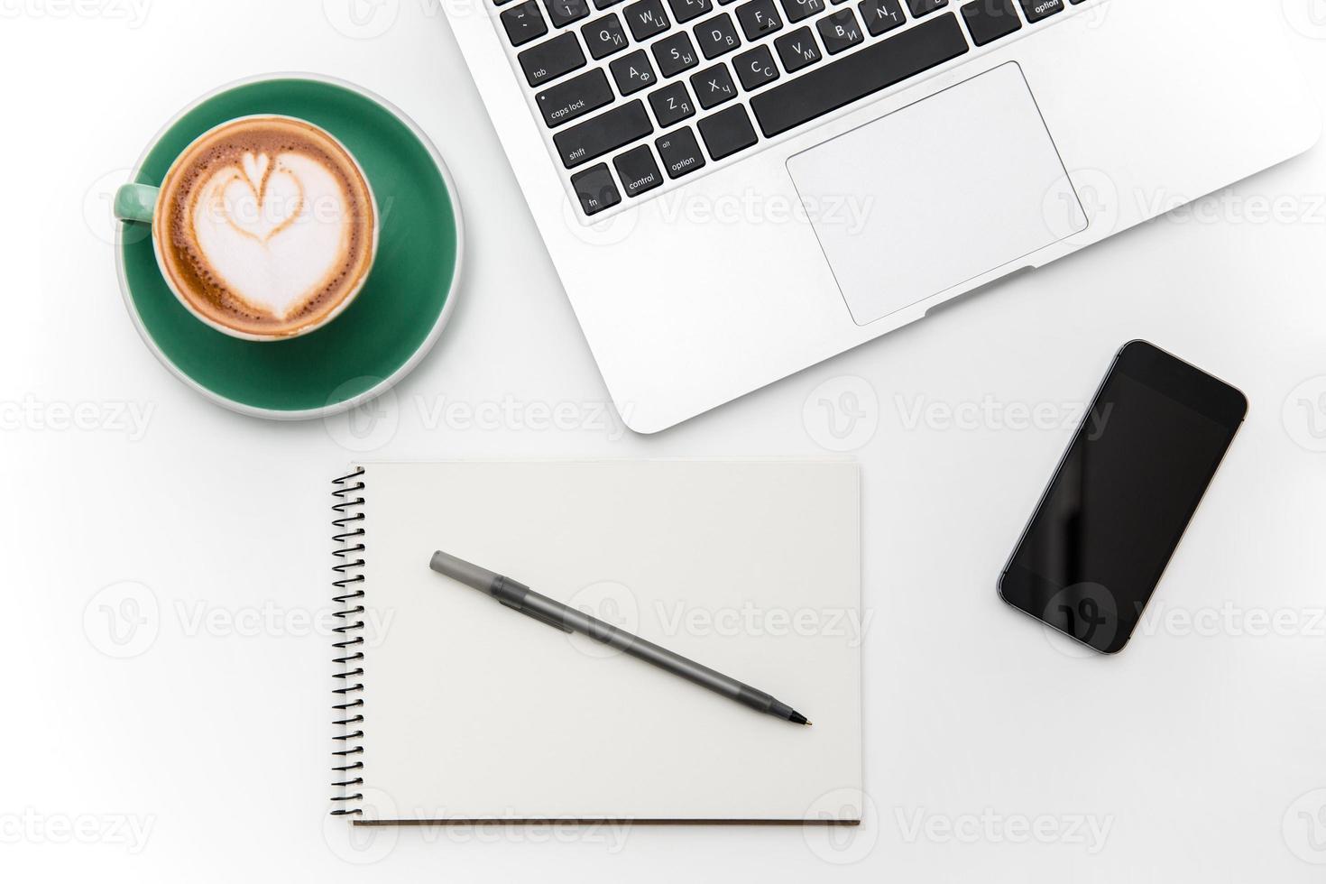 Laptop, Handy mit leerem Bildschirm, Tasse Kaffee, Notizblock und Stift foto