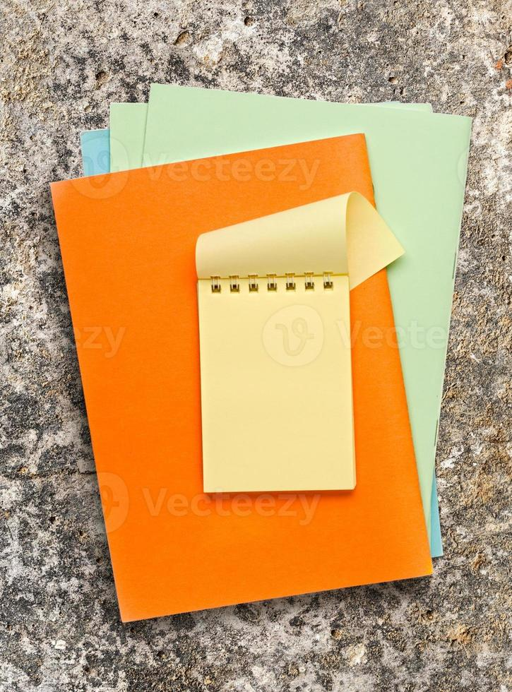 Öffnen Sie den gelben Notizblock auf farbigem Papier foto