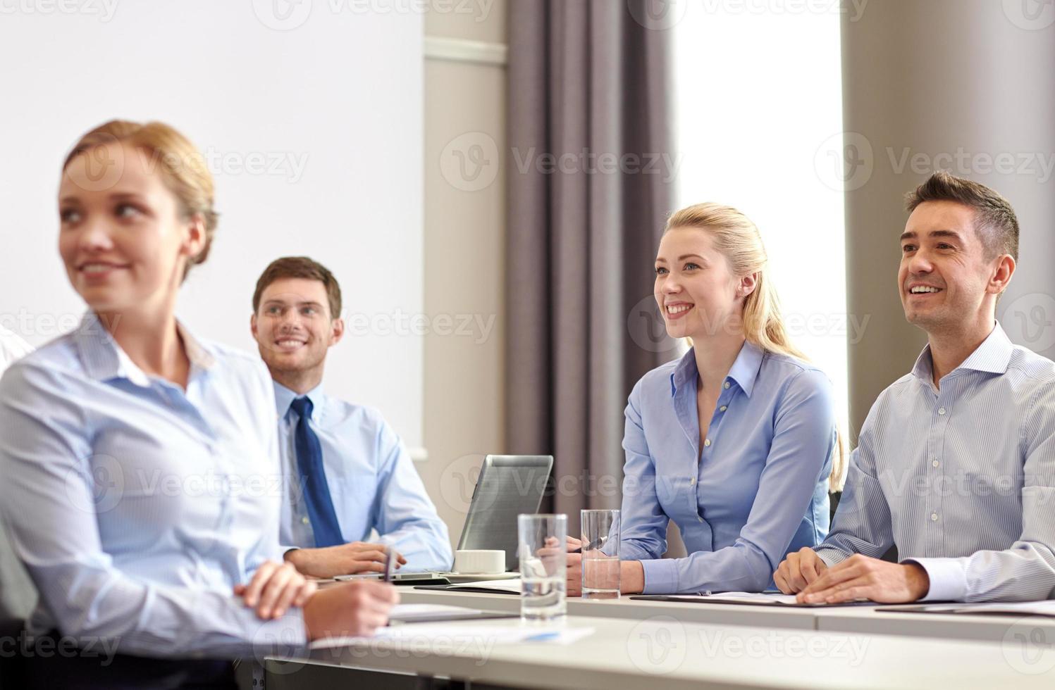 Gruppe lächelnder Geschäftsleute, die sich im Büro treffen foto