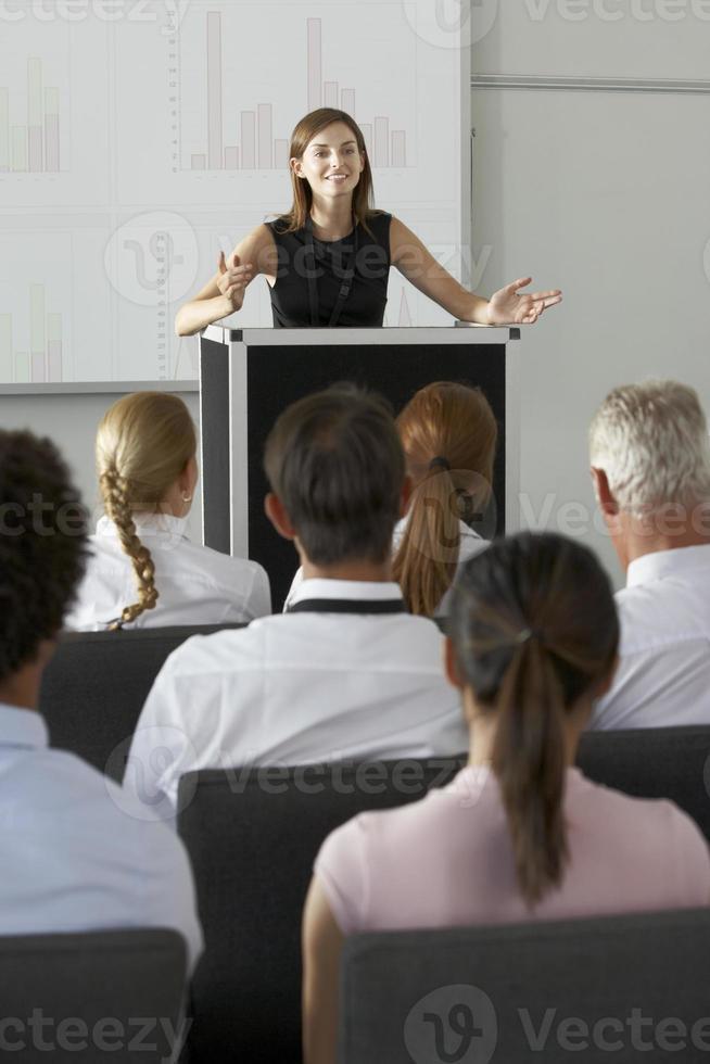 Geschäftsfrau, die Präsentation vor einem Podium liefert foto