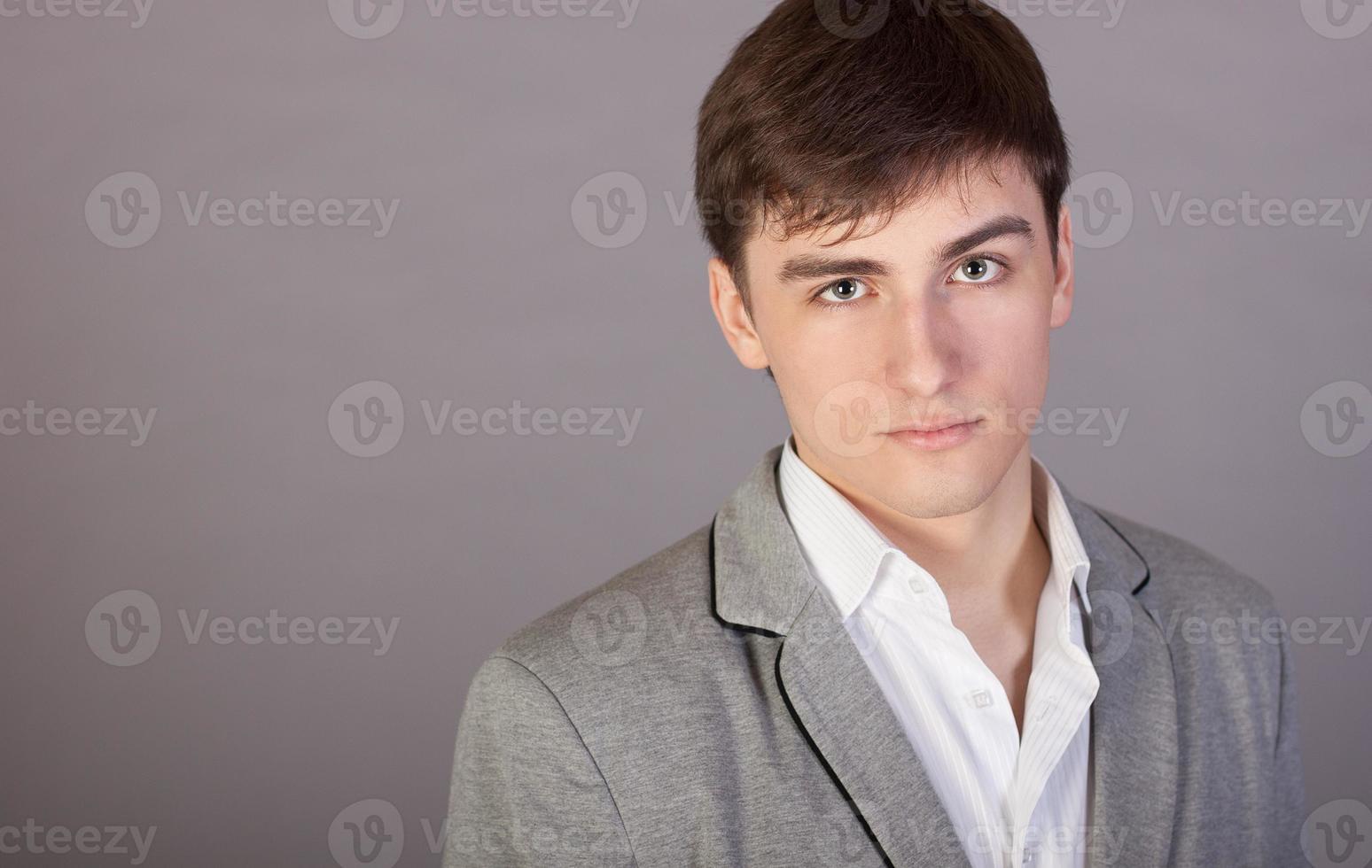 stilvoller junger Geschäftsmann auf einem grauen Hintergrund foto