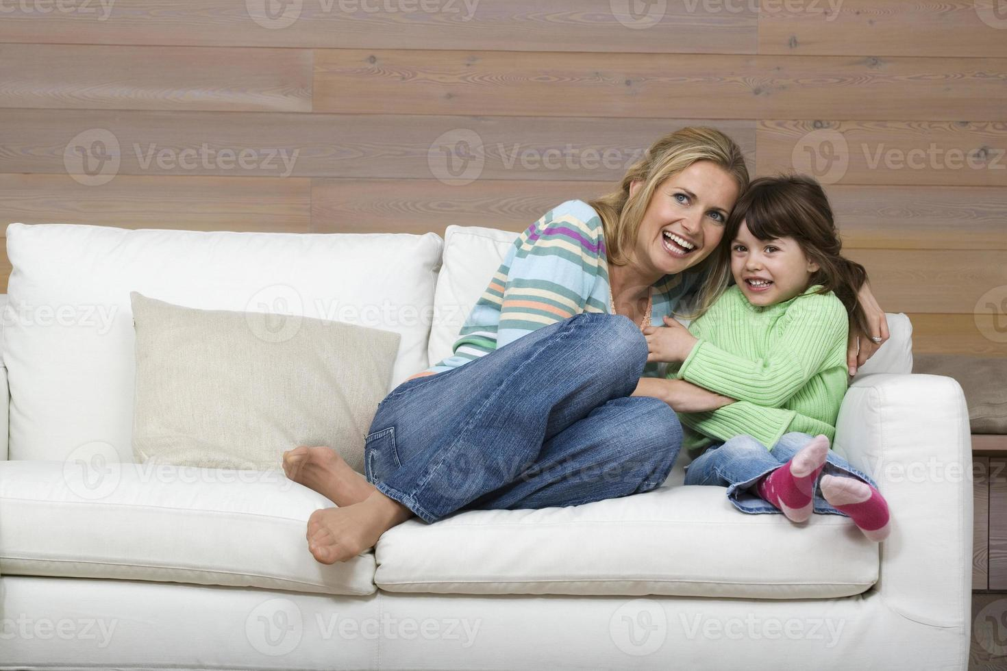 Mutter und Tochter sitzen auf dem Sofa und umarmen lächelnd foto