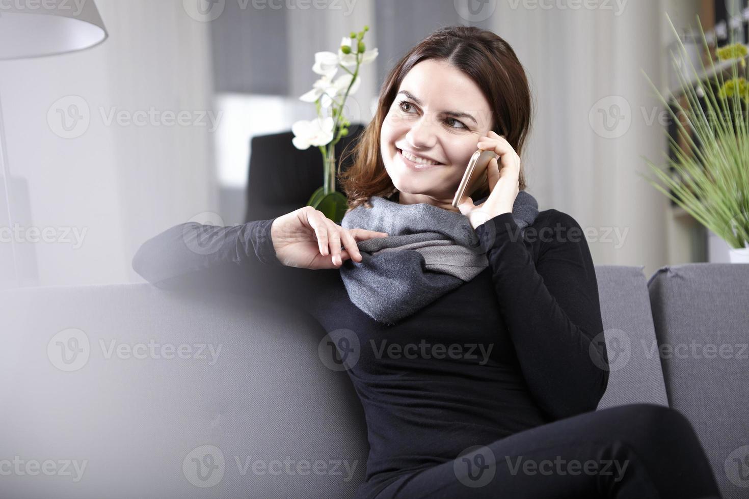 Brünette Frau sitzt auf der Couch und telefoniert foto