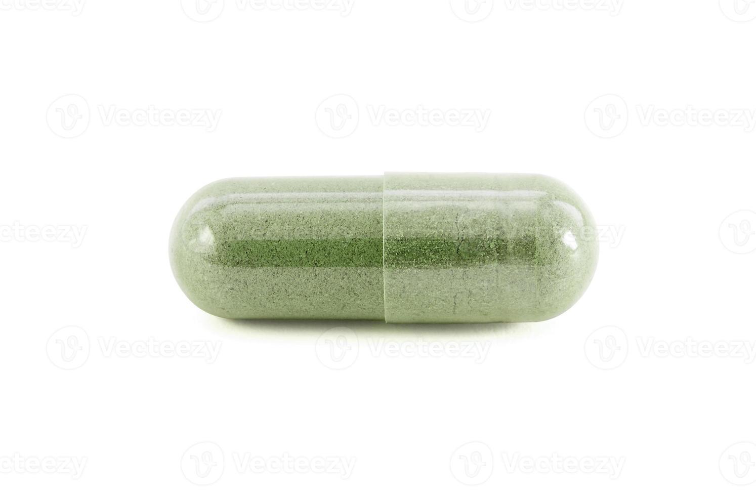 Kapsel des grünen Kräuterzusatzprodukts isoliert auf Weiß foto