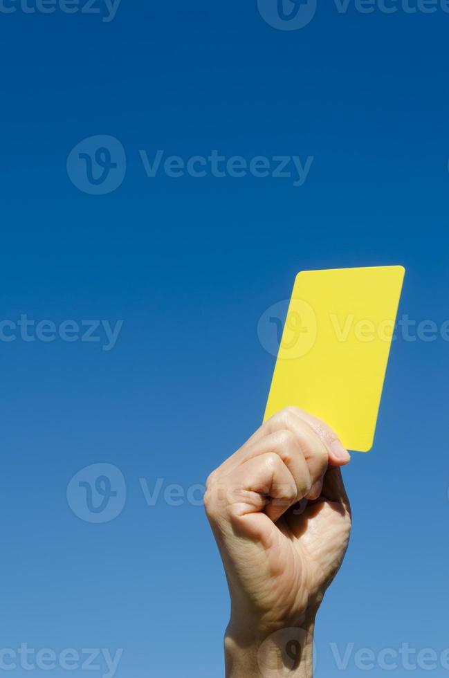 gelbe Karte in der Hand gegen blauen Himmel foto