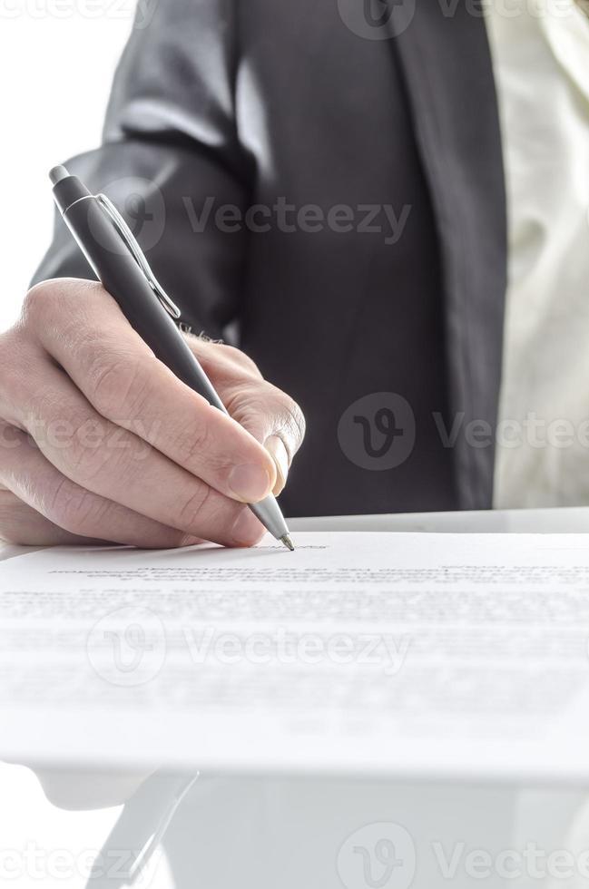 Geschäftsmann, der Nahaufnahme unterschreibt foto
