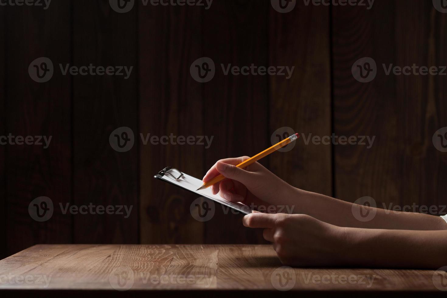 Nahaufnahme der Hand der Frau, die auf Papier über Holztisch schreibt foto
