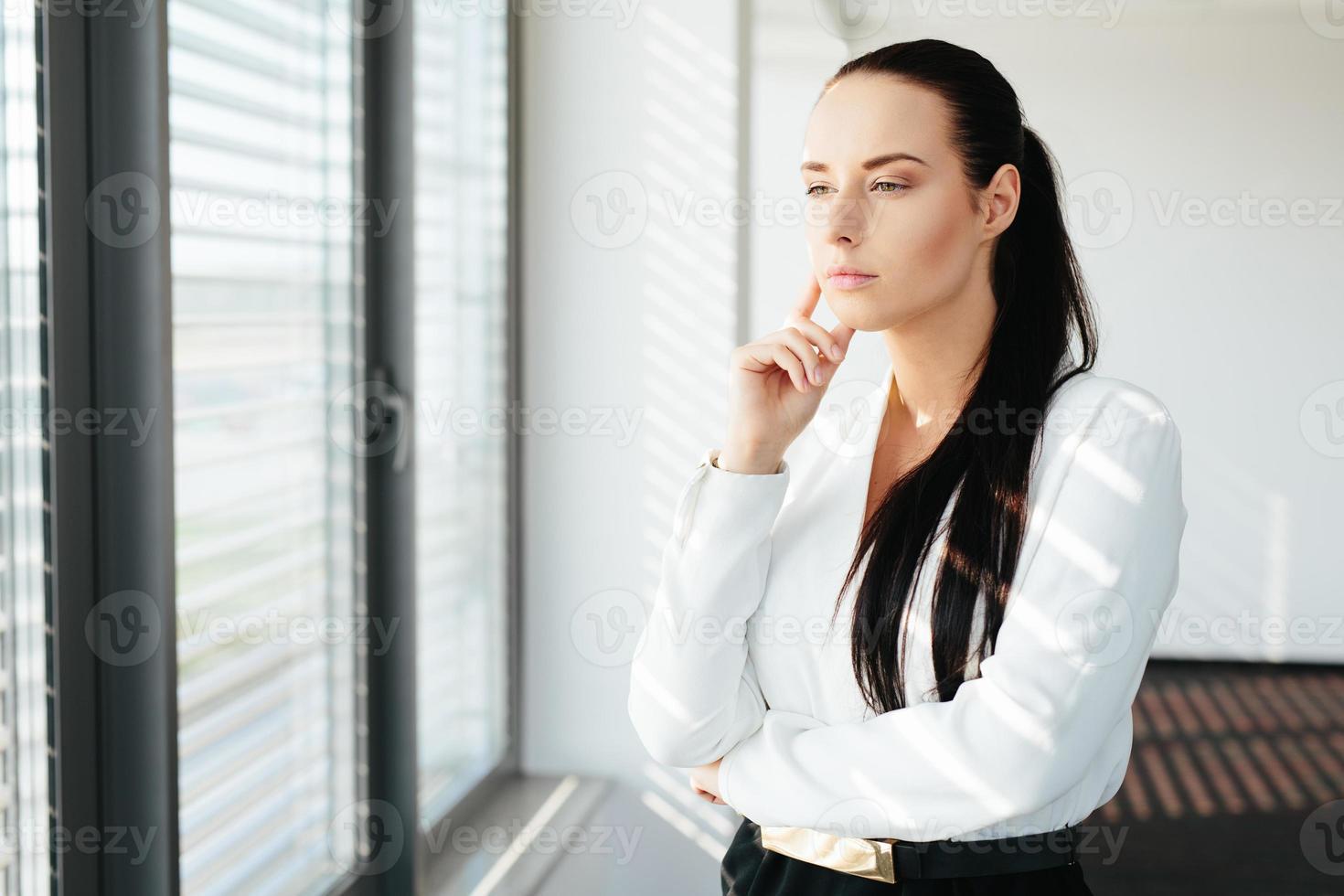 weibliche Führungskraft, die am Fenster steht und durch es schaut foto