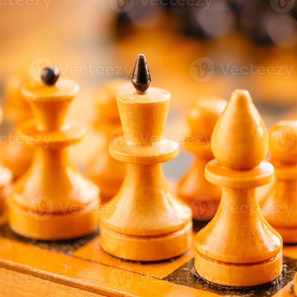 altes hölzernes Schach, das auf Schachbrett steht foto