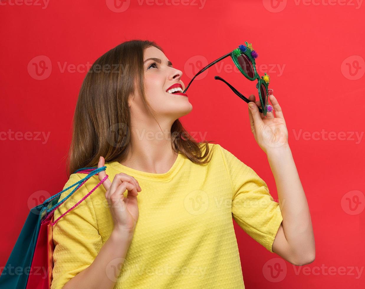 Frau mit Weihnachtsfeiergläsern und Einkaufstüten foto