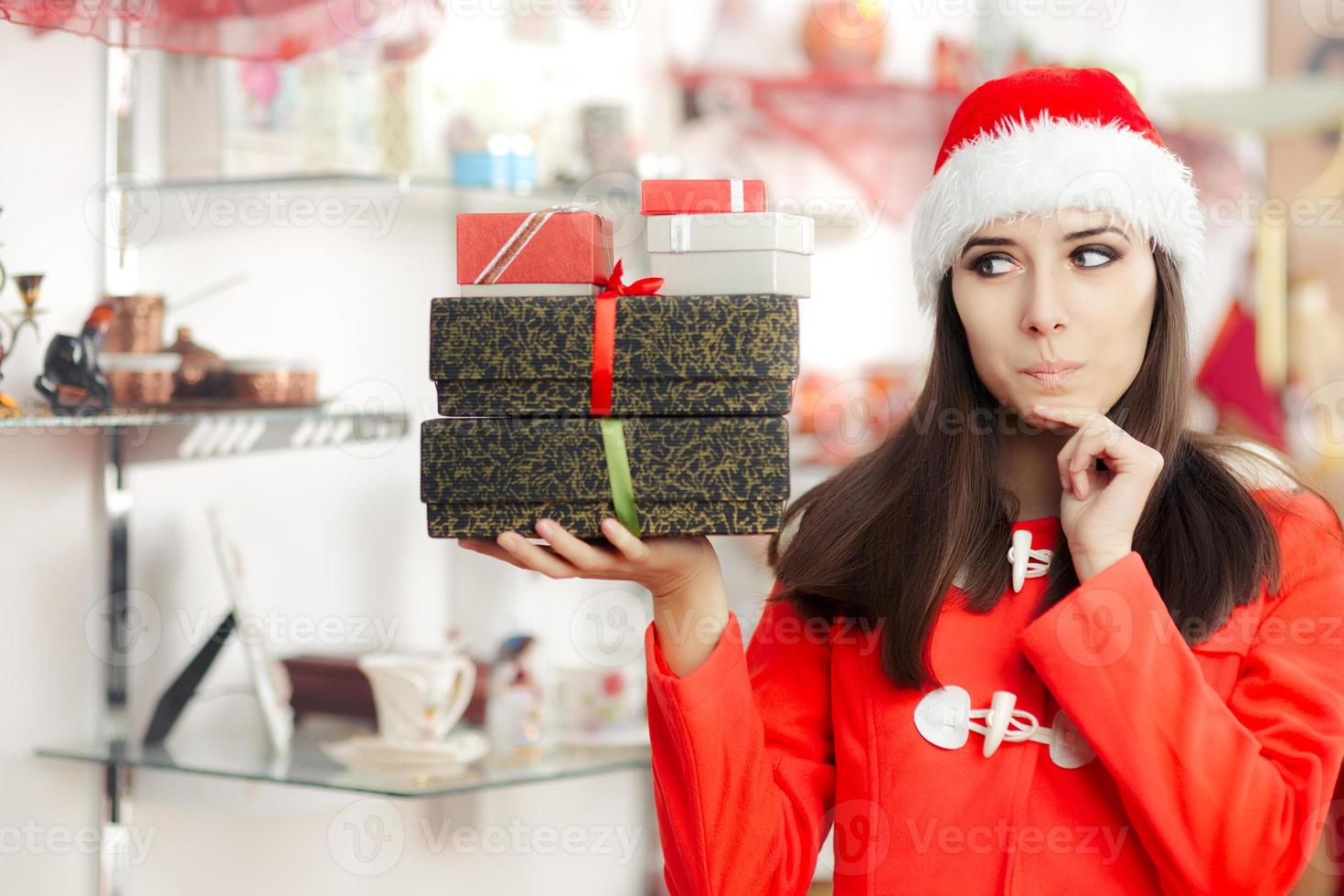 neugieriges Weihnachtsmädchen mit Geschenken im Geschenkeladen foto