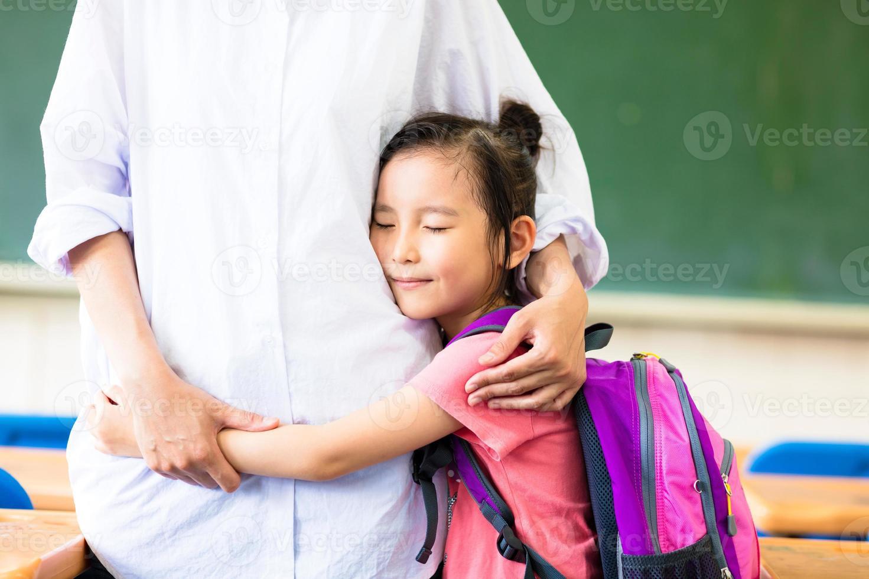 glückliches kleines Mädchen, das ihre Mutter im Klassenzimmer umarmt foto