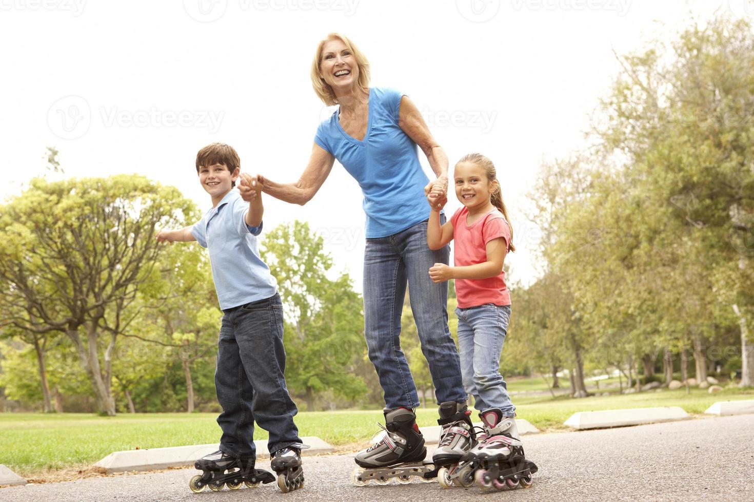 Großmutter und Enkelkinder laufen im Park Schlittschuh foto