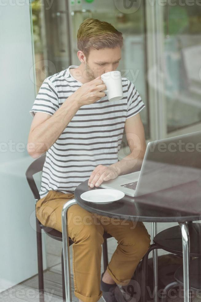 lächelnder Student, der heißes Getränk trinkt foto