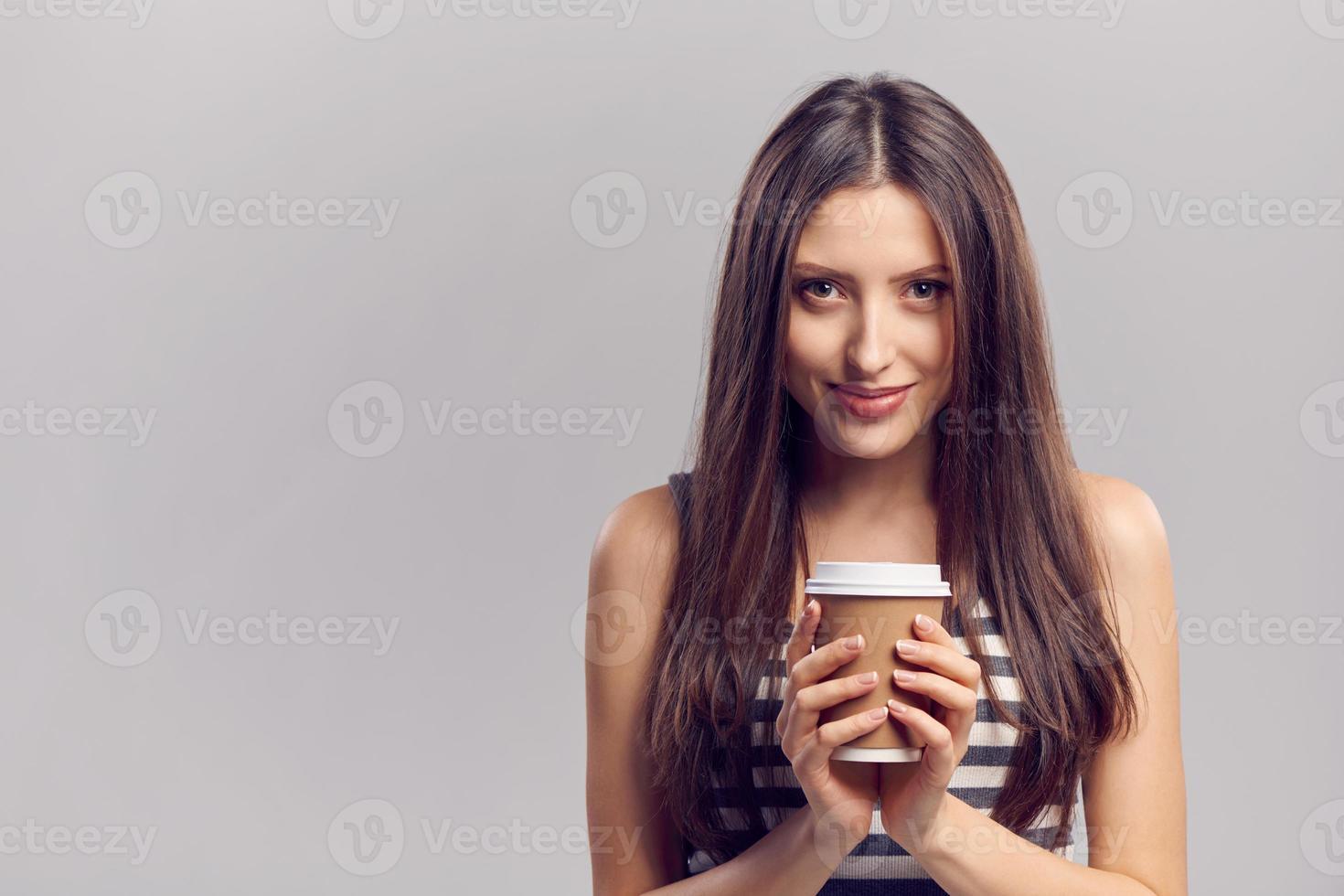 Frau trinkt heißes Getränk aus Einweg-Pappbecher foto