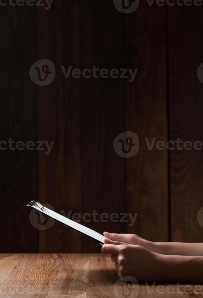 Frauenhand, die Papier über Holztisch hält foto
