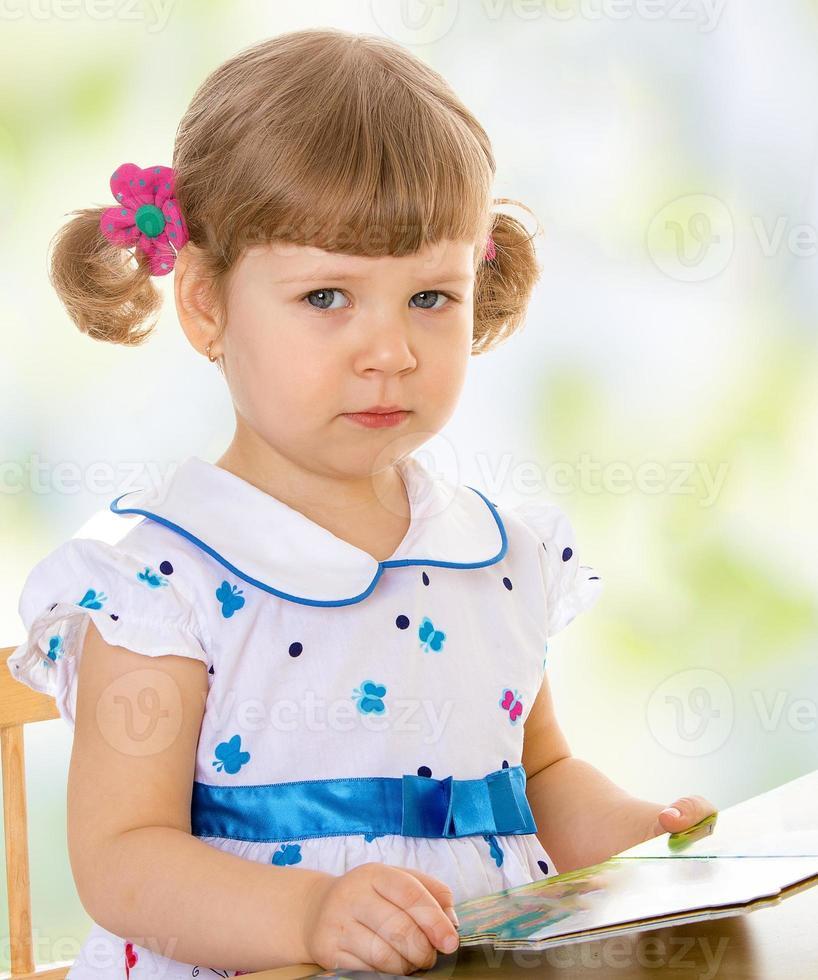 sehr kleines Mädchen liest ein Buch foto