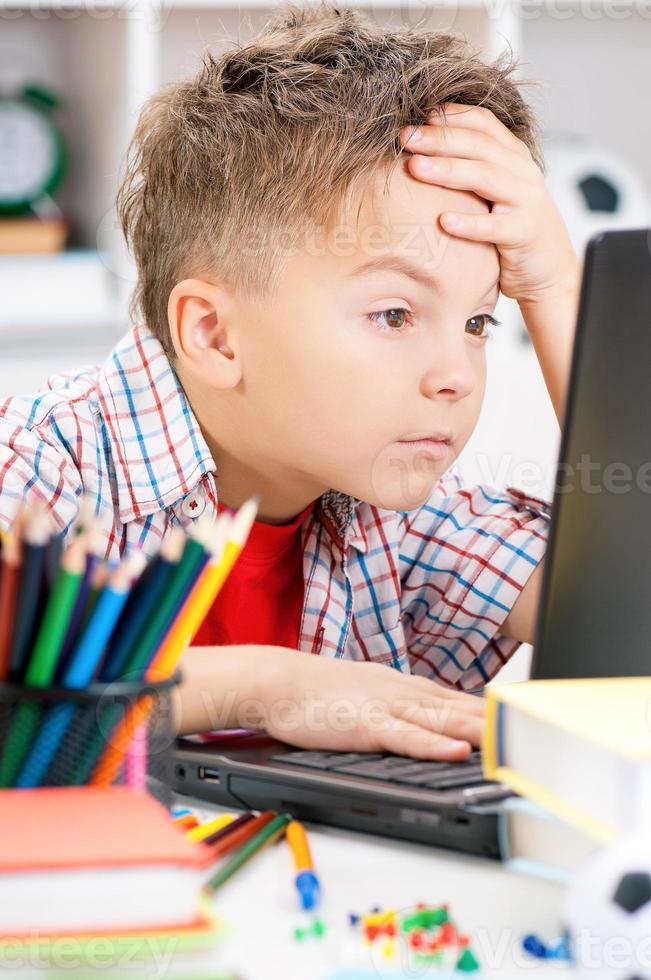 Junge macht Hausaufgaben foto