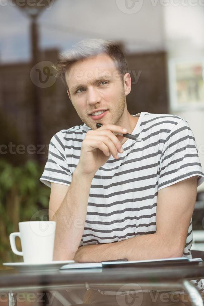 denkender Student, der mit einem heißen Getränk sitzt foto