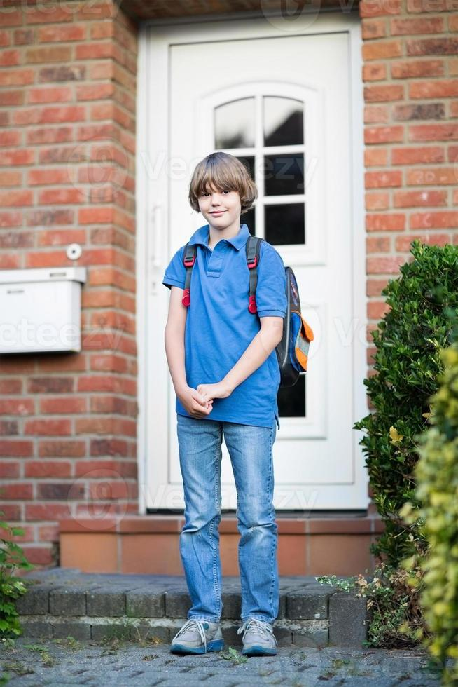 süßer Studentenjunge, der das Haus zum ersten Schultag verlässt foto