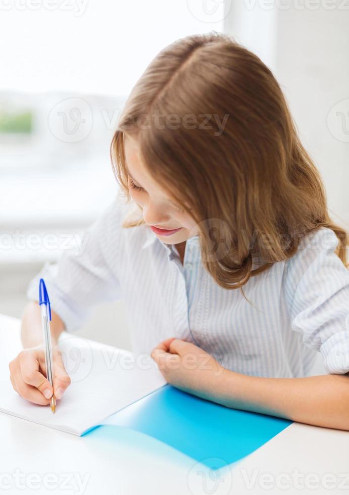 Studentin, die in der Schule im Notizbuch schreibt foto
