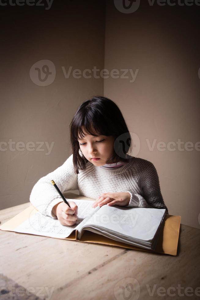 Schulmädchen macht ihre Schularbeiten, Hausaufgaben foto
