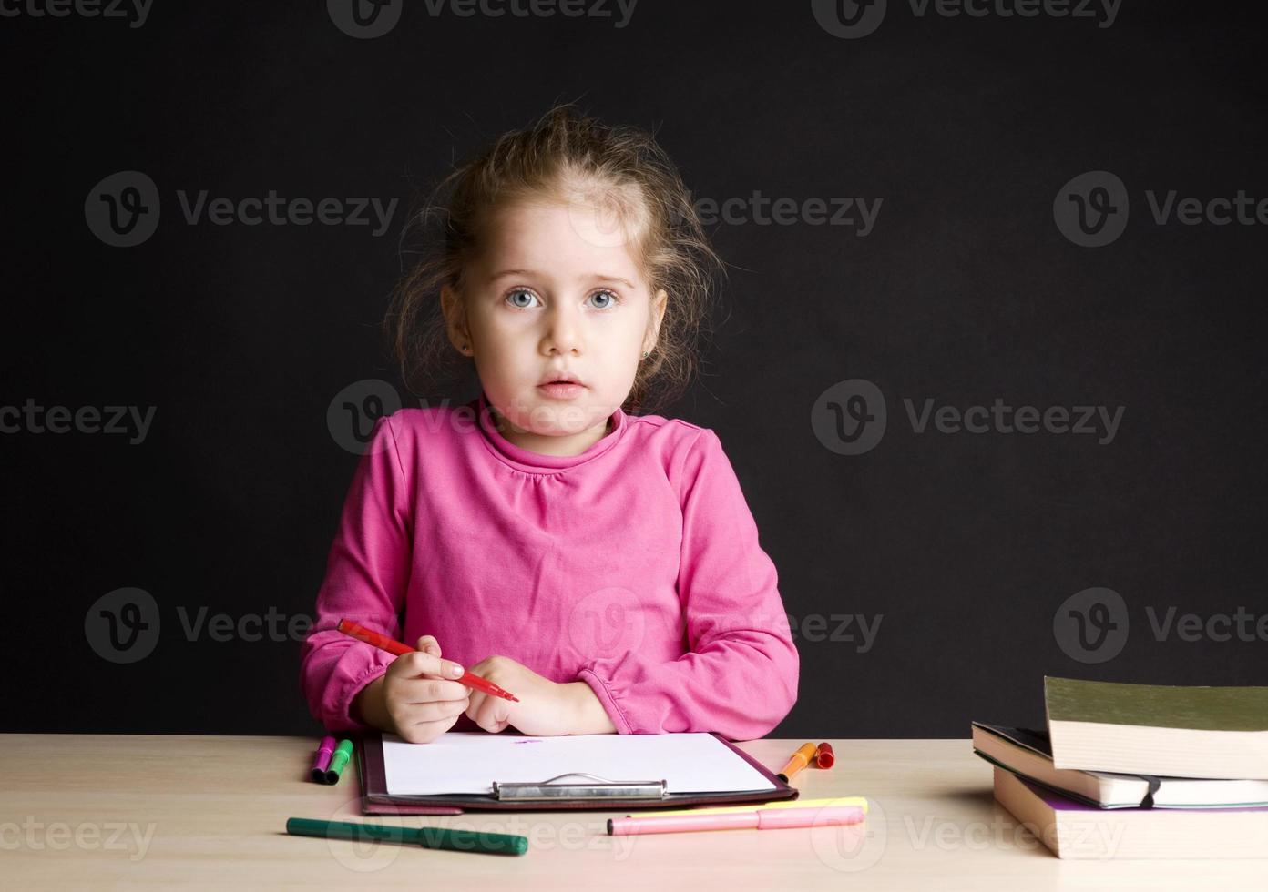 kleines Mädchen, das im Unterricht zeichnet foto