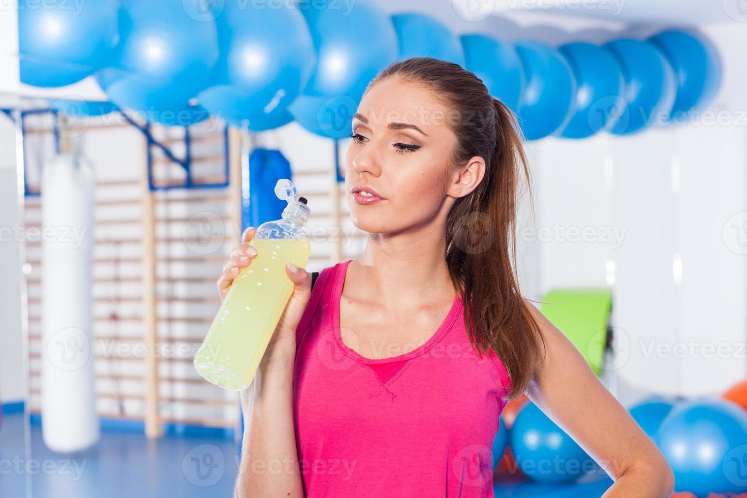 junges Mädchen trinkt isotonisches Getränk, Fitnessstudio. Sie ist glücklich. foto