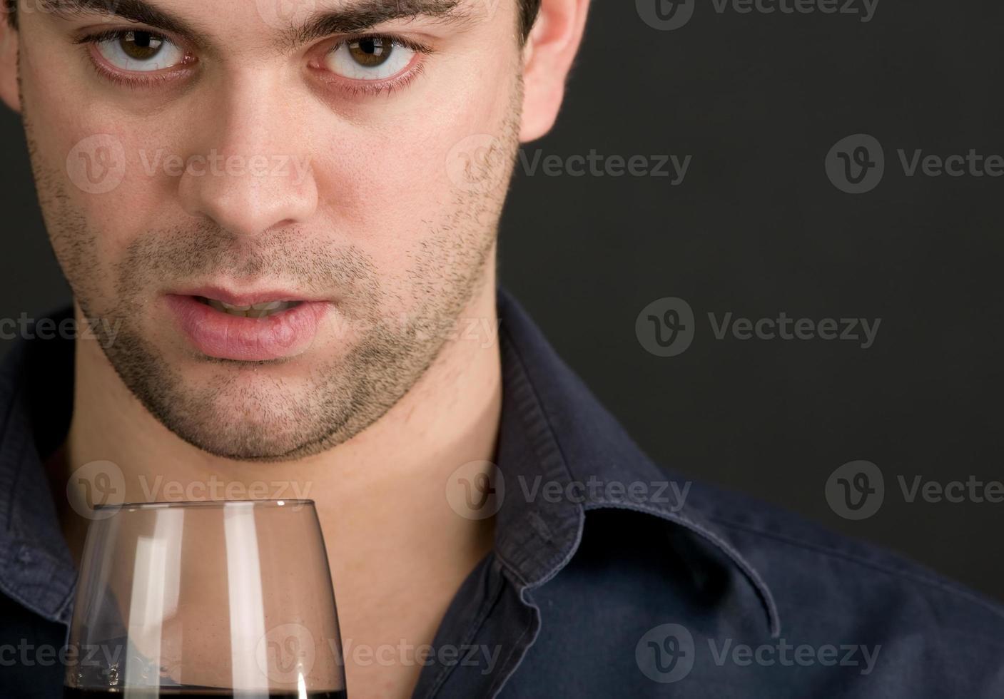 junger Mann, der Wein trinkt foto