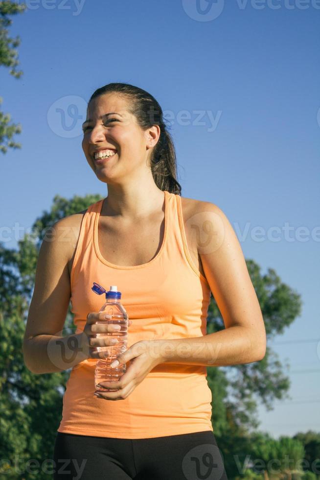 Frau lacht und trinkt Wasser foto