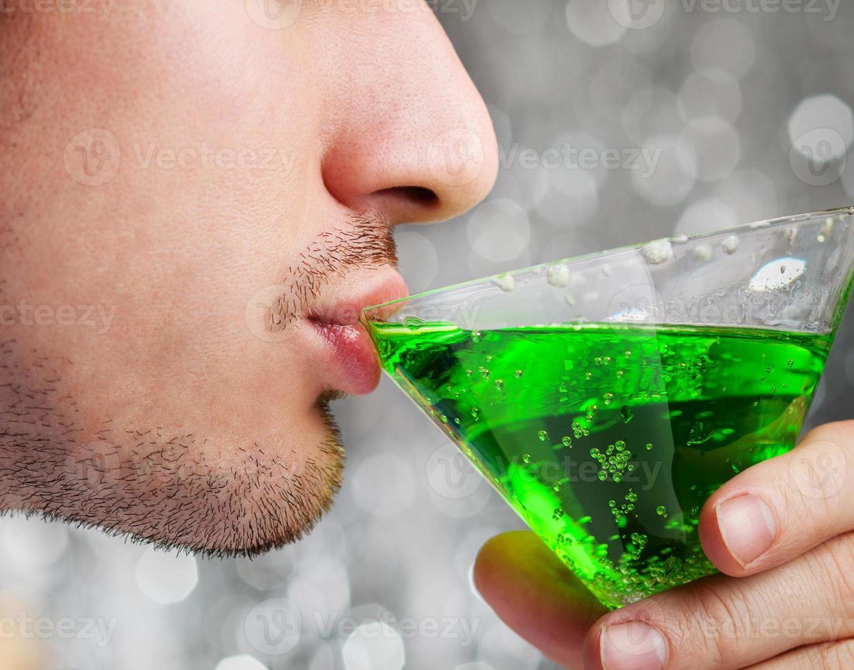 Mann trinkt grünen Alkohol Cocktail foto